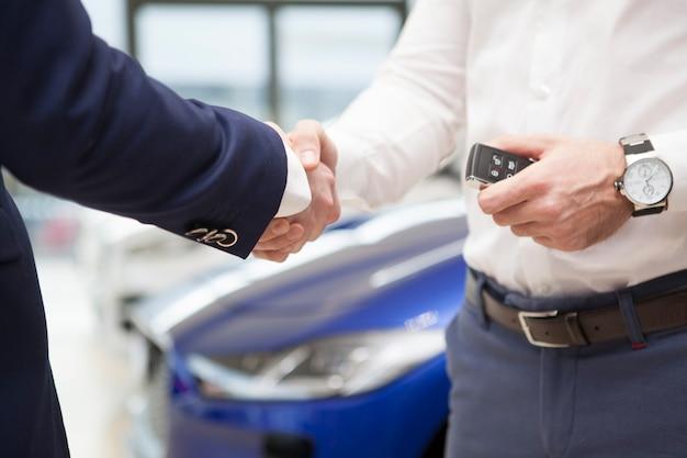 Mann, der autoschlüssel vom verkäufer am händler erhält