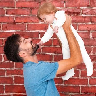 Mann, der baby mit ziegelsteinhintergrund hält