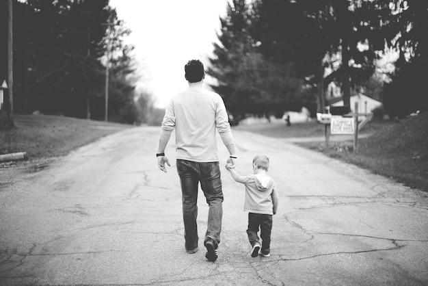 Mann, der babys hand hält