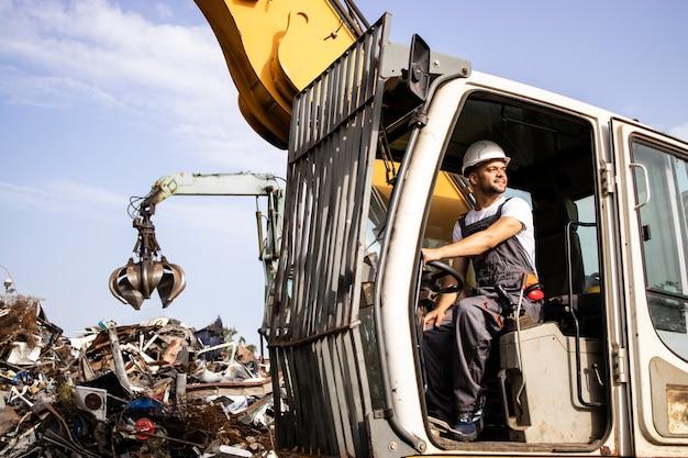 Mann, der bagger-industriemaschine zum heben von metallschrott auf schrottplatz betreibt