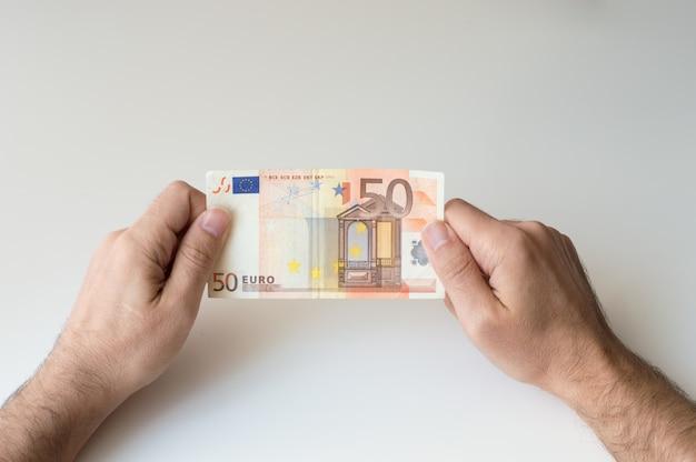 Mann, der banknote des euro fünfzig in seinen händen hält