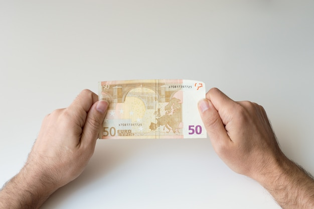 Mann, der banknote des euros fünfzig in seinen händen hält