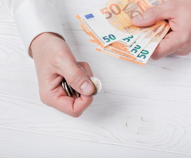 Mann, der banknoten und münzen hält