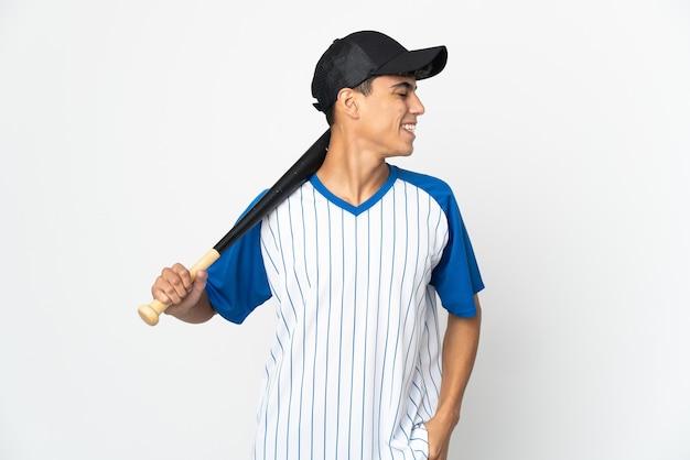 Mann, der baseball auf isoliertem weißem lachen in seitlicher position spielt