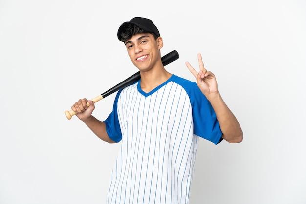 Mann, der baseball auf isoliertem weißem lächeln spielt und siegeszeichen zeigt