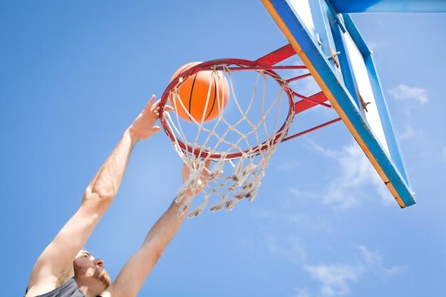 Mann, der basketball auf der straße spielt