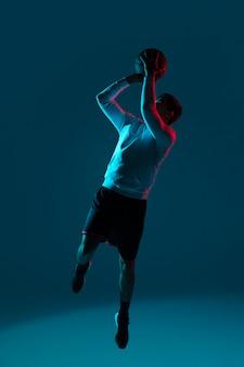 Mann, der basketball mit kühlen lichtern spielt