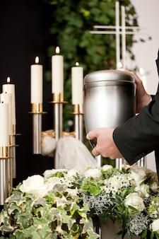 Mann, der begräbnisurne mit kerzen und blumen nimmt
