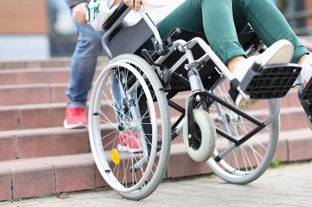 Mann, der behinderte frau im rollstuhl nach oben zieht, nahaufnahmeprobleme der ungehinderten bewegung von