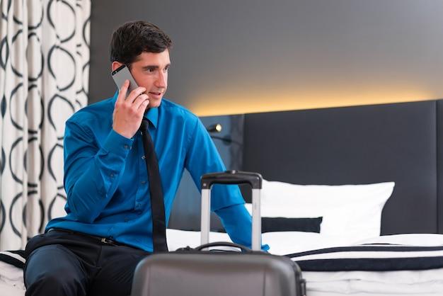 Mann, der bei der ankunft im hotelzimmer telefoniert