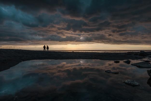 Mann, der bei sonnenaufgang auf der linie des horizonts fischt