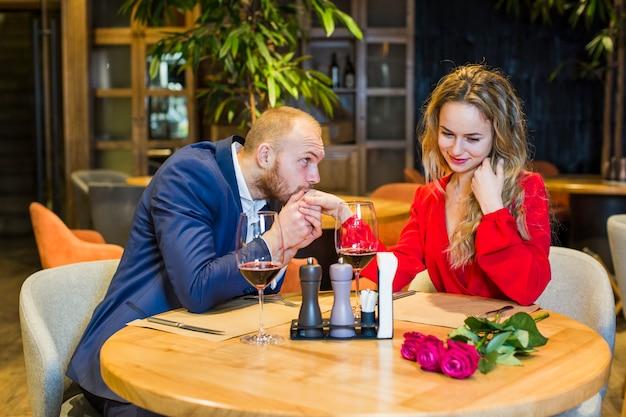 Mann, der bei tisch frauenhand im restaurant küsst