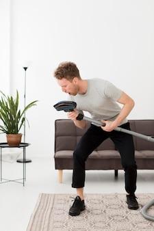 Mann, der beim reinigen am vakuum singt