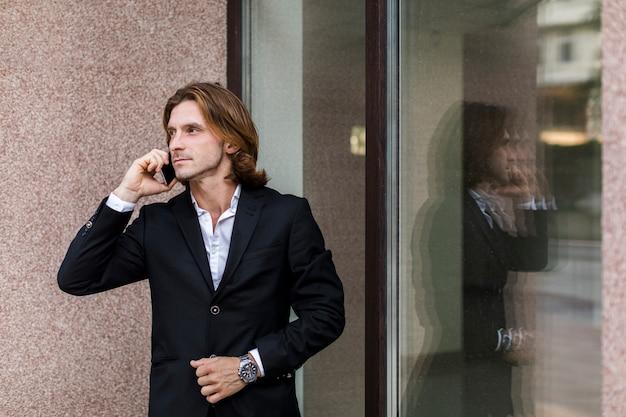 Mann, der beim sprechen am telefon weg schaut