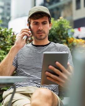 Mann, der beim sprechen an einem telefon sitzt