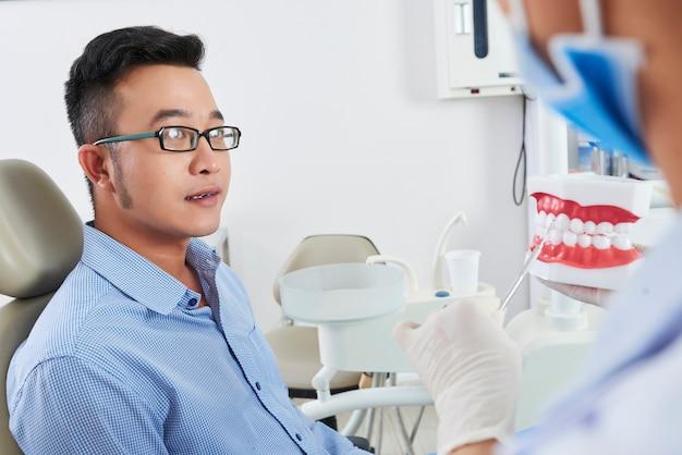 Mann, der beratung bei zahnarzt hat
