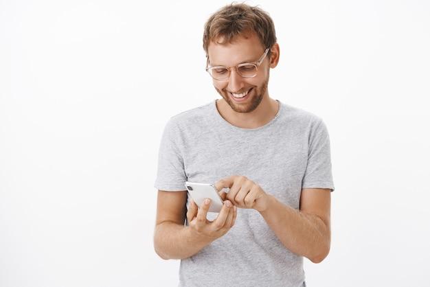 Mann, der berührt und entzückt wird, videos auf dem smartphone vom letzten urlaub erneut anzuschauen, freudig lächelnd auf dem bildschirm des gerätebildschirms auf dem gerät mit dem zeigefinger, der über der weißen wand unterhalten wird
