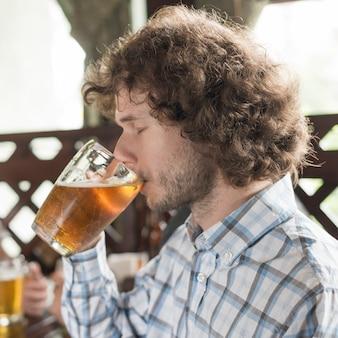 Mann, der bier mit geschlossenen augen trinkt