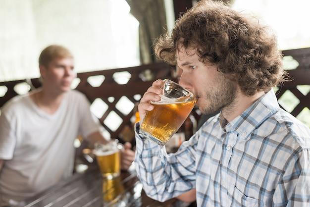 Mann, der bier nahe freunden in der kneipe genießt