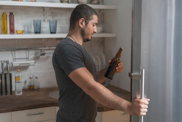 Mann, der bier vom kühlschrank nimmt