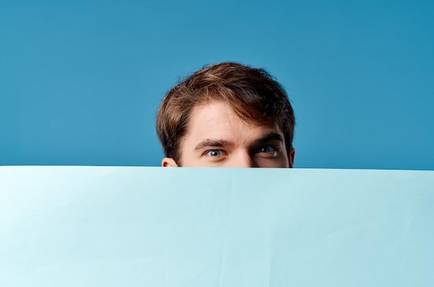 Mann, der blauen hintergrund der blauen fahnenwerbung des blauen hintergrunds hält. hochwertiges foto