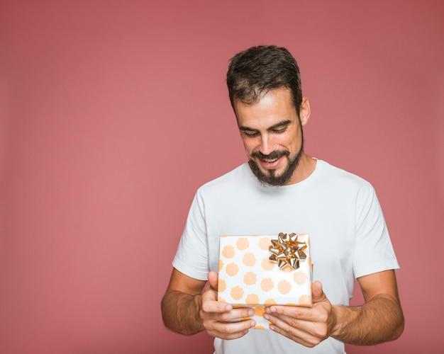 Mann, der blumengeschenkbox mit goldenem bogen gegen farbigen hintergrund betrachtet