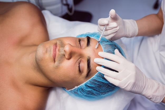 Mann, der botox-injektion auf seiner stirn erhält