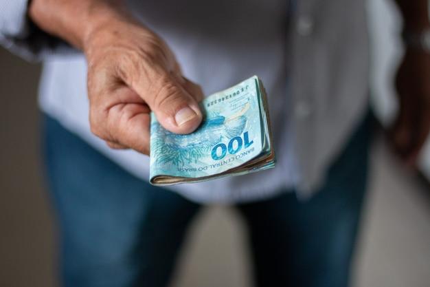 Mann, der brasilianische geldbanknoten von hand hält.