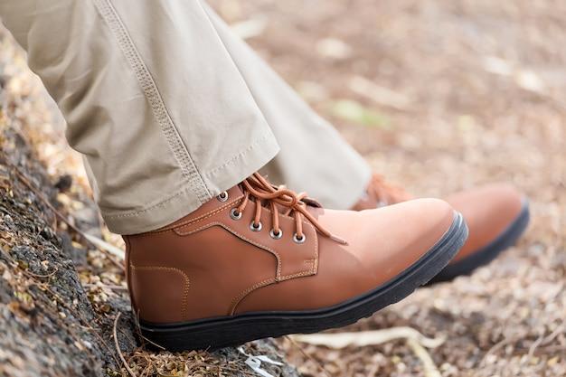 Mann, der braune frachthosen trägt und im naturpark sitzt