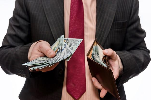 Mann, der brieftasche mit dollarbanknoten auf weißer wand zeigt