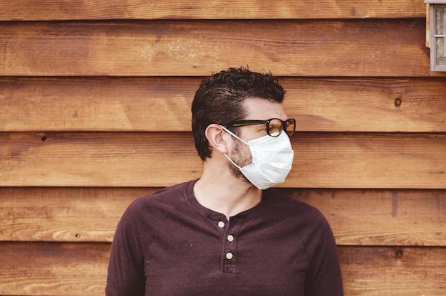 Mann, der brille und eine hygienische gesichtsmaske vor einer holzwand trägt