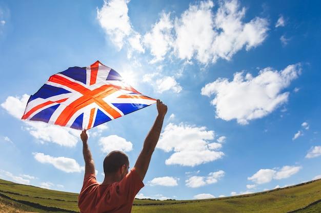 Mann, der britische flagge in der landschaft fliegt