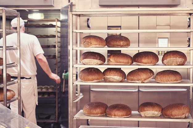 Mann, der brot in der bäckerei backt