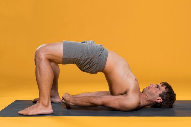 Mann, der brückenhaltung auf yogamatte tut