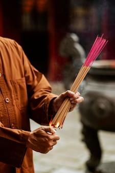 Mann, der bündel weihrauch am tempel beleuchtet