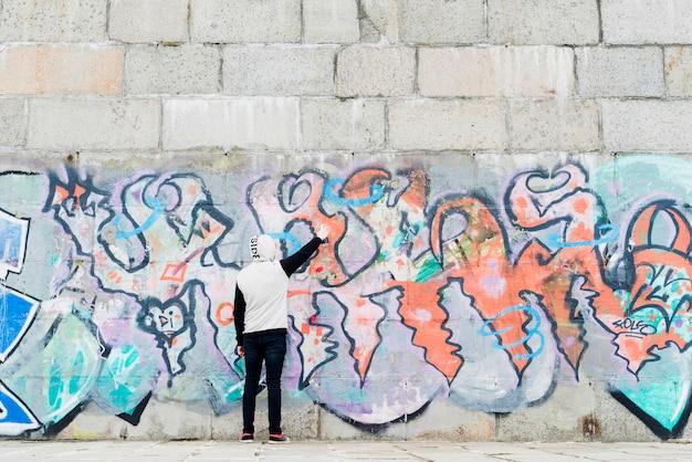 Mann, der bunte graffiti auf wand malt