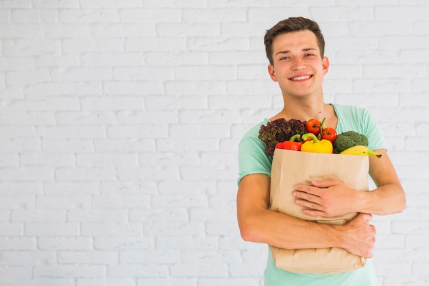 Mann, der buntes frischgemüse in der lebensmittelgeschäftpapiertüte hält