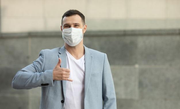 Mann, der chirurgische maske trägt, grüßt mit seiner hand über dem herzen