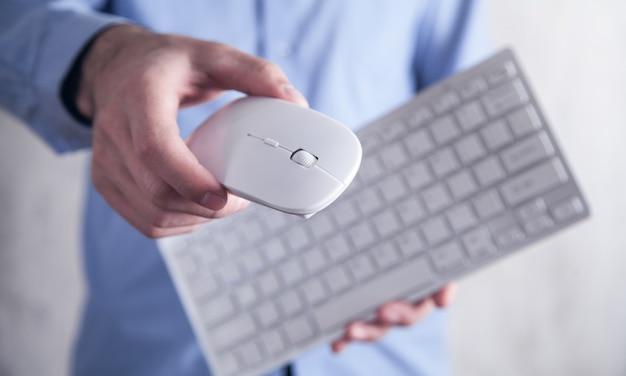 Mann, der computermaus mit einer tastatur hält. technologie, wirtschaft