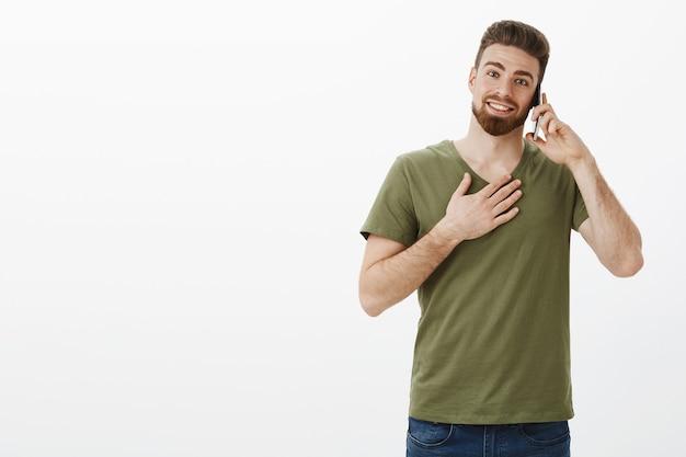 Mann, der dankbar und erfreut empfängt, telefonanruf zu erhalten, der auf smartphone spricht, das mit bday über handy beglückwünscht wird, das hand auf brust dankbar hält und glücklich über weiße wand lächelt