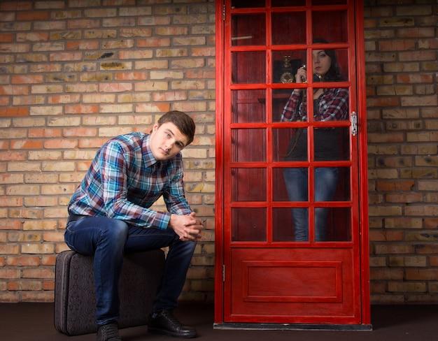 Mann, der darauf wartet, dass seine freundin aufhört, an einem öffentlichen telefon zu sprechen, der mit einem gelangweilten gesichtsausdruck auf seinem koffer sitzt, während sie mit freunden plaudert