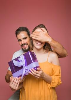 Mann, der das Auge ihrer Freundin versteckt, das Geschenkbox gegen farbigen Hintergrund hält