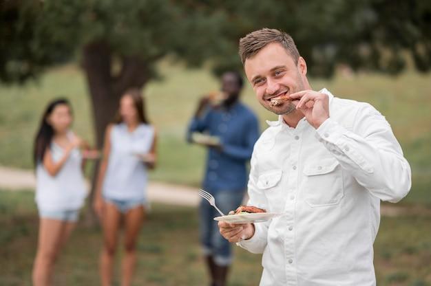 Mann, der das essen an einem grill genießt