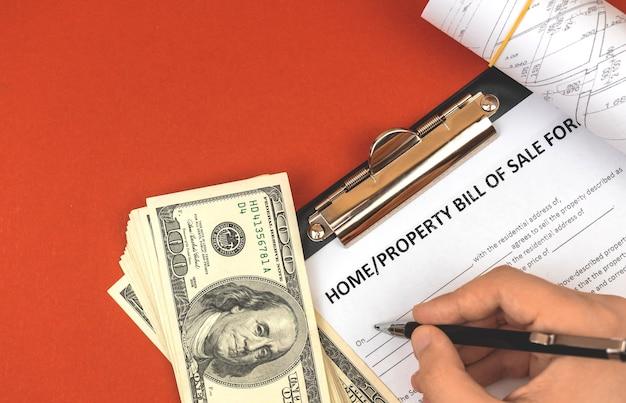 Mann, der das formular für den kaufvertrag ausfüllt. dokumente zu geld- und immobilienprojekten. foto von oben auf dem bürotisch