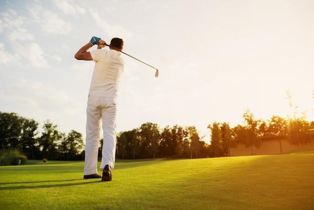 Mann, der das golf nimmt schwingen geschossen auf einem rasen spielt.