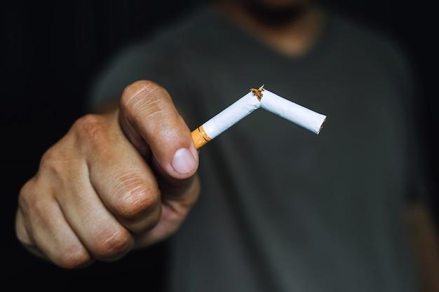 Mann, der das halten der zigarette in der hand ablehnt. rauchverbot konzept.