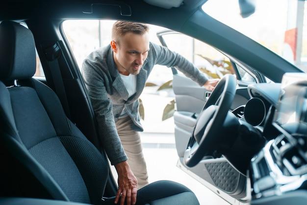 Mann, der das innere des neuen autos im ausstellungsraum beobachtet