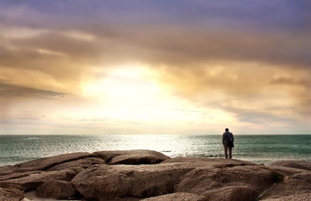 Mann, der das meer steht auf seesteinen gegenüberstellt