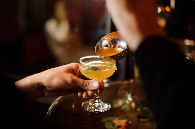 Mann, der das orangenlimonadengetränk in das glas gießt