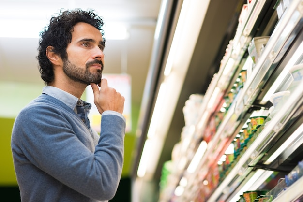 Mann, der das rechte produkt in einem supermarkt wählt
